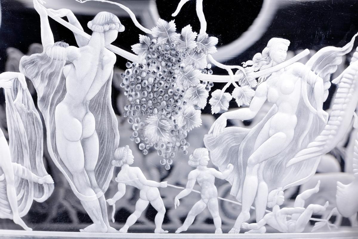 """""""Bacchuståget"""" av Simon Gate, graverad skål med antikiserande motiv i form av vinguden Bacchus anförandes en vintunna dragen av två tigrar, och efter honom ett helt tåg av festande nakna kvinnor, barn och män. Bacchuståget tillhör en av Orrefors mest ikoniska föremål, och var en del i brukets framgångar under 1920-talet."""
