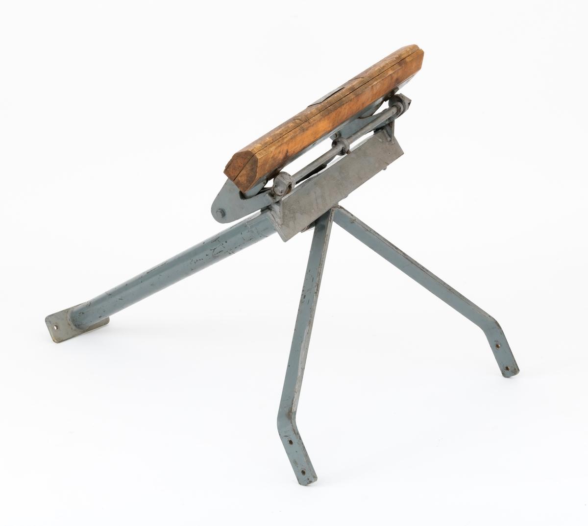 """Filkrakk (arbeidsbukk), klemme, klype til sagbladfiling, svansfiling. Klemma, filkrakken,  gikk under betegnelsen """"Skogforsøksvesenets klemme for filing av svans"""". En slik filkrakk brukes når sagbladet trenger full oppsetting og justering, filing og vigging (viking). Utstyret består av et stativ, ramme, konstruert i grålakkert stålrør og flatjern. På toppen av stativet, stålrørssøylen,  gjenfinnes klemma, klypa, som sagbladet, svansbladet, spennes fast i når det skal files og vigges (vekselsvis utbøying av sagtennene, slik at saga ikke setter seg så lett fast i sagskåret). Denne klemma består av to deler i treverk som klemmes mot sagbladet, svansbladet. Ved hjelp av hendler strammes klemmas to deler sammen slik at sagbladet holdes fastspent under filingen. Ramma, stativet,  kan f. eks. skrus fast i en vegg eller benk og forankres i golvet. (Det er hull for skruer i foten av stattivet til forankring i golv.)  Det kan tyde på at utstyret først og fremst er tenkt brukt i et verksted. Klemma kan roteres og vinkles, slik at en får riktig arbeidsstilling og filevinkel under arbeidet med sagbladet. Brukeren får slik en stabil arbeidsbukk, krakk, når saga skal vedlikeholdes. En slik filkrakk brukes når saga trenger mer enn det daglige vedlikeholdet."""