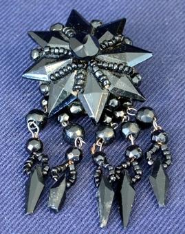 Av svart sten slipad till att få en kantig yta, formad till en stjärna med åtta uddar, i mitten en rund pärla från vilken det går sex rader med småpärlor. Mellan varje udd sitter runda pärlor. Broschens baksida består av en rund papplatta klädd med tyg, i vilken en säkerhetsnål är fäst, med vilken man fäster broschen i klädesplagget. I baksidan är fäst med trådar fem stycken hängen bestående av pärlor med olika form, sammanbundna med metalltråd.