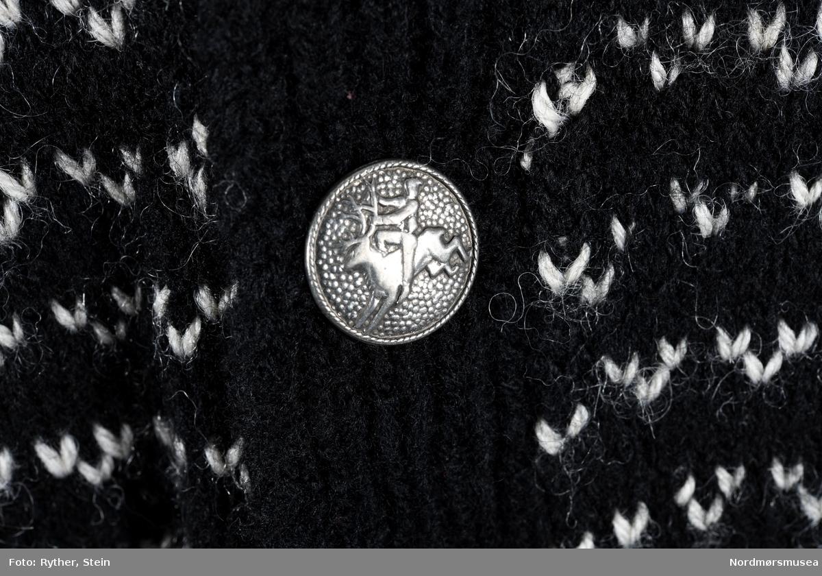 Strikkejakke / kofte i svart og hvitt mønster. 8 sølvknapper med figur av en person som rir på et reinsdyr.