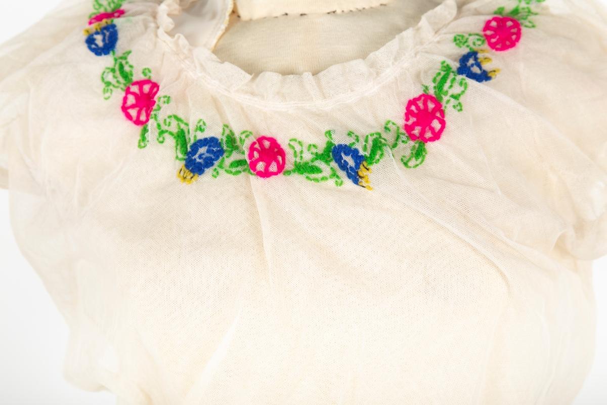 """Kjole sydd av to lag tyll. . Korte puffermer.Rund, vid hals med smal skråkappe (1,5 cm) rynket sammen med snor. Korte puffermer. Understelaget av tyll fasongsydd, øverste laget drapert over.Overdel og skjørt rynket i livet. Blomsterranke i halsen. 2 små buketter festet på skjørtet. Underskjørt har kniplingsblonde nederst.Flerfarget blomsterbroderi i ullaktig tråd rumdt halsringing og som 2 buketter på skjørtet Fanny har fortalt at hun brukte et bredt rosa lett mlnstre silkebånd i livet; hun kalte det """"drømmeband""""  Tilstand: litt skjør.  Fanny A. hadde oppvekst på gårdem Gaavim i Kroer, Ås, som gift på gården Østby  Produksjonsted Oslo, Molstad (motebutikk) Opplysning fra Fanny."""