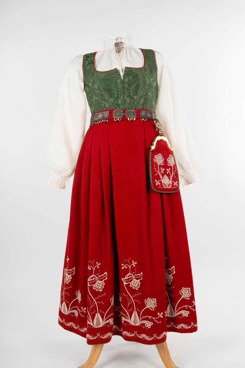 Follo kvinnebunad  Follobunad, kvinne. Foldelagt skjørt med ullbroderi, liv i silkedamask, forkle og skjorte i lin, lue og løslomme. Se FHM. 12081.a-i. Hovedfarge rød eller blågrønn.