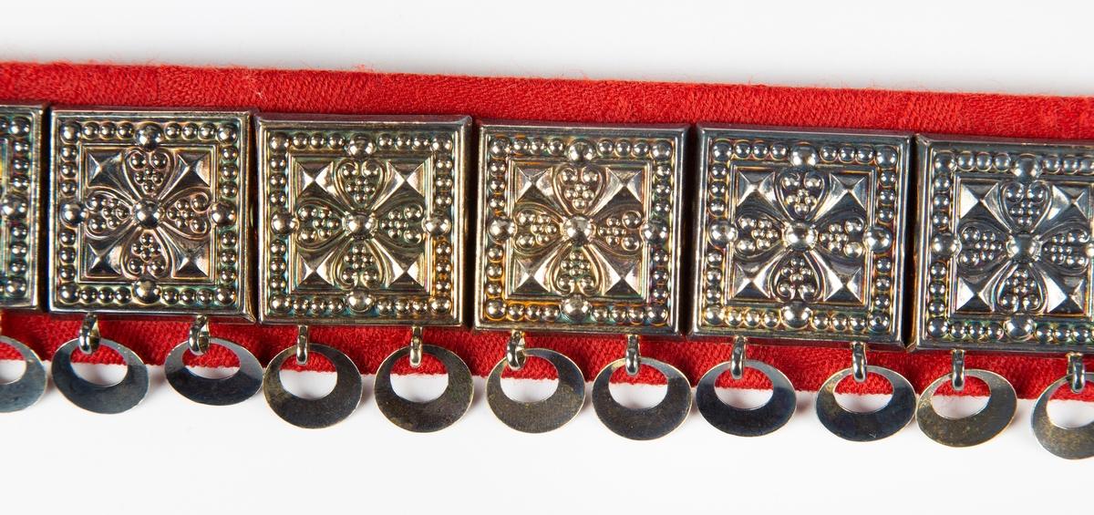 Stølebeltebelte til Follo kvinnebunad. Rød ulldamask, 22 firkantede støler med åpne ringer er av forgylt sølv. 2 runde støler midt forran med krok og hempe.  Det kan brukes stølebelte til bunaden. Det har spenne og firkantede støler av forgyldt sølv. Under stølene er det heng formet som åpne ringer. Sølvdelene er festet til et belta av stakkestoffet. Bunadnemnda har bestemt at stølebeltet skal brukes av voksne kvinner.