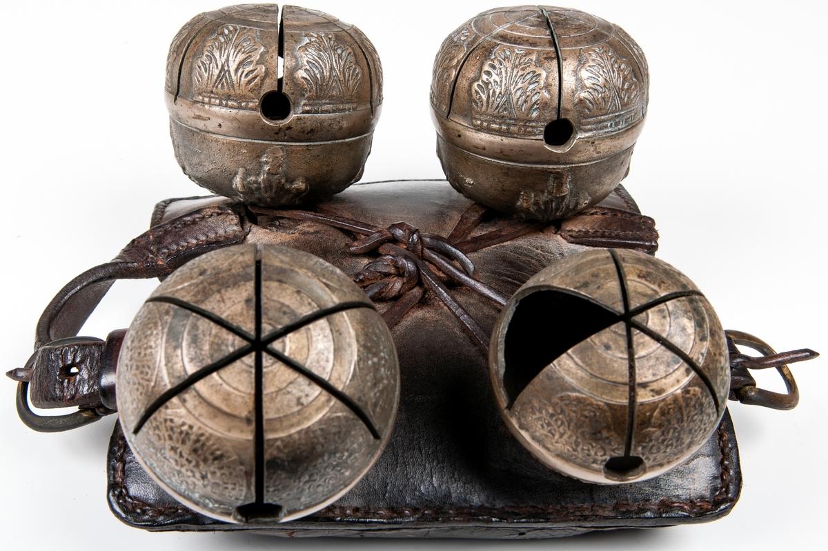 Bjällra. Fyra pinglor på brunt läder. Mönster på pinglorna.