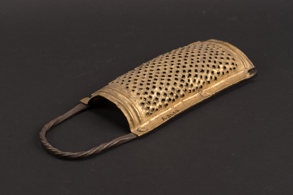 Rektangulärt, bukigt, rivjärn av mässing fäst på kantskenor av järn. Kantskenorna bildar även det böjda och vridna handtaget. Järnet är dekorerat med inpunsade prickar och några vulster, hålen är spikade.