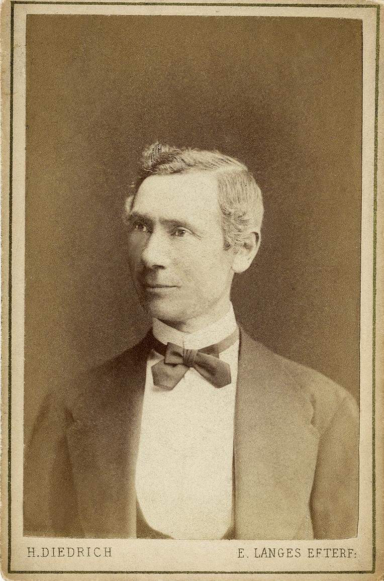 Porträttfoto av en medelålders man i kavajkostym med väst, stärkkrage och fluga.  Bröstbild, halvprofil. Ateljéfoto.