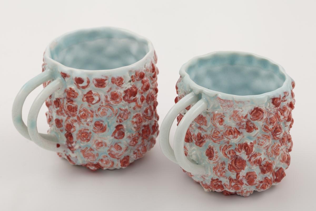 To lyseblå porselenskopp dekorert med røde prikker. Konvekse bobler utgjør kopenes overflatestuktur, hvor boblene er rødglaserte og danner et dekorativt mønster som kan minne om roser. Koppene har to tynne hanker plassert tett sammen.