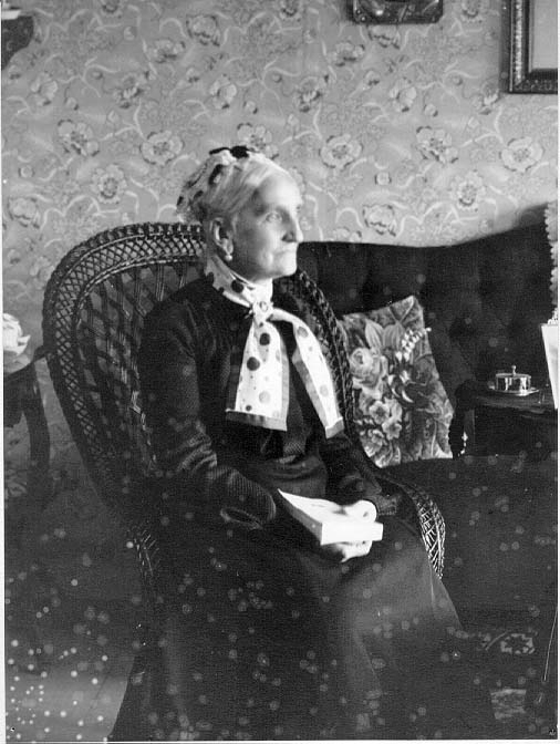 Fru Charlotte Fahnehjelm sittande i en korgstol med hög rygg i en hemmiljö. En scarf med kulörta prickar i olika storlekar runt halsen. Hon håller en bok i knät.