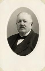 Foto av en äldre man med mustascher, klädd i mörk kostym med