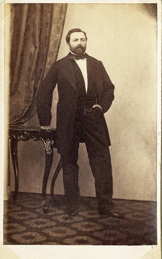 Foto av en skäggig man, klädd i mörk bonjour med väst, stärkkrage och fluga. Han lutar ena handen lätt mot ett bord.  Till vänster syns ett draperi.  Helfigur, halvprofil. Ateljéfoto.