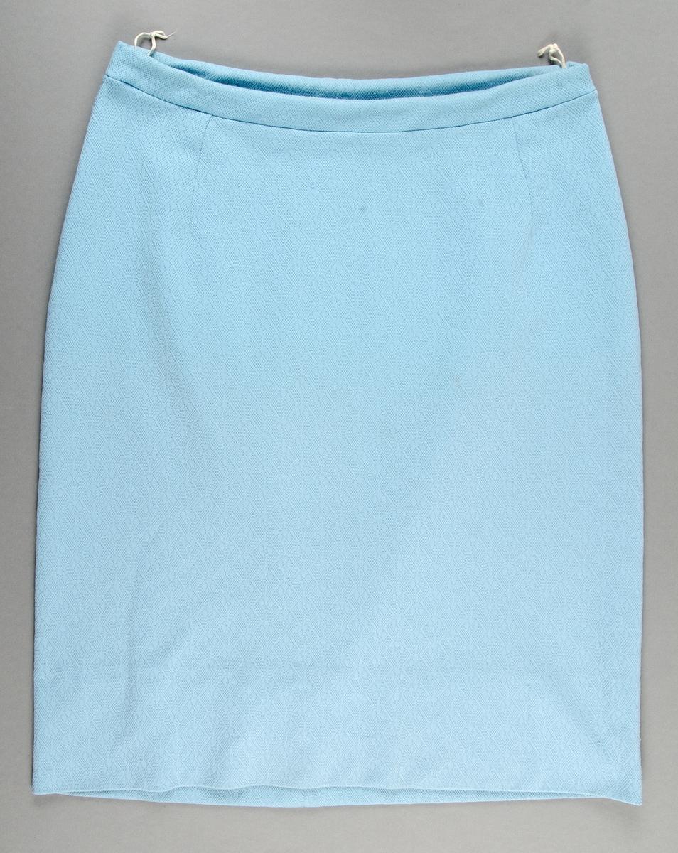 Tvådelad klänning av ljusblå konstfibertrikå. Maskinsydd. Tvådelad: överdel och kjol. Överdel: knäppning framtill med fem knappar i samma tyg. Två små blindfickor. Rundad halslinning. Kjol: resår i midjan. Mått: längd 61,5 cm, ärmlängd 31 cm, kjollängd 61,5 cm, vidd 109 cm.