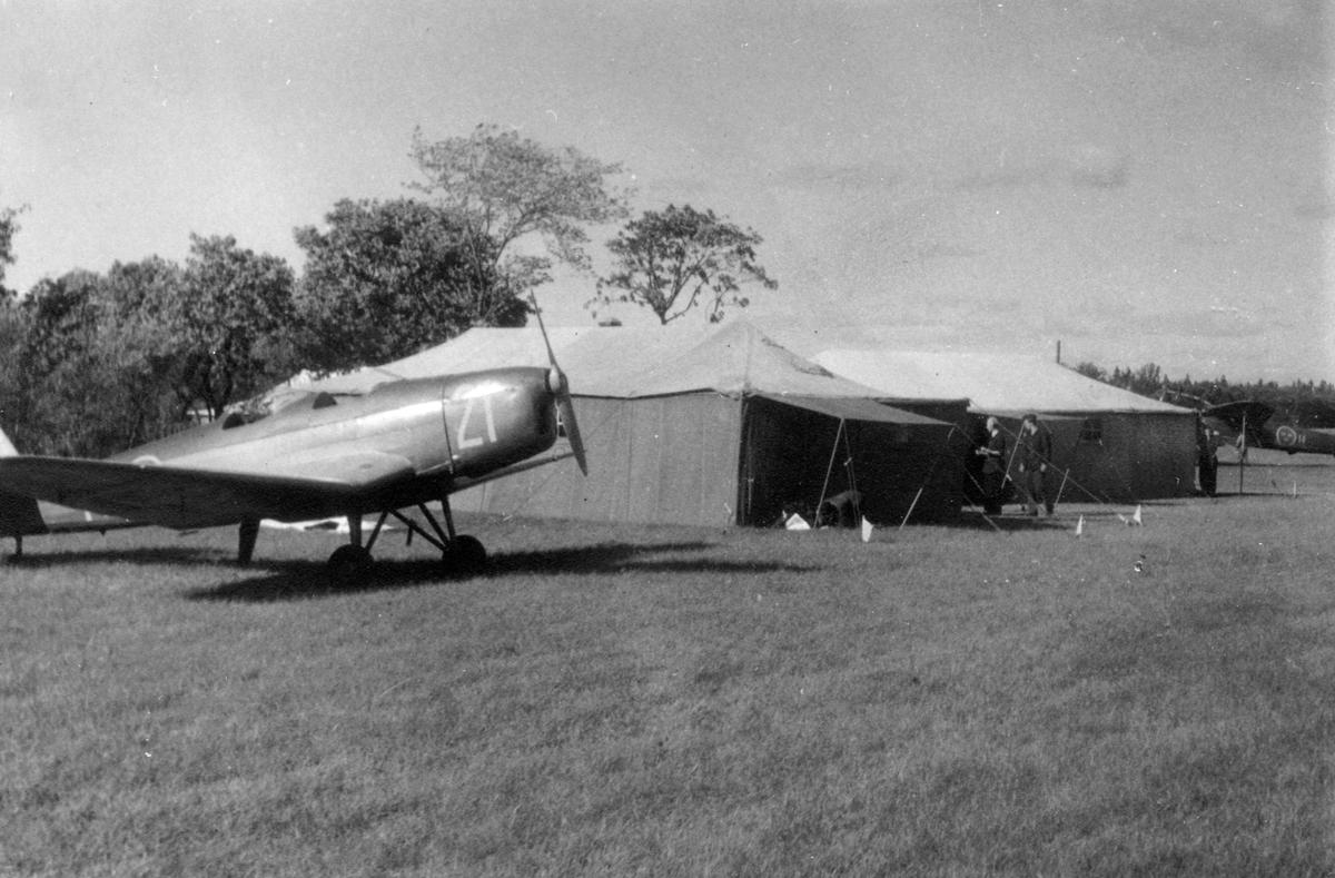 Flygplan Sk 25 uppställd på ett flygfält bredvid tälthangarer, 1940-tal. I bakgrunden syns ett par flygmekaniker och flygplan Saab B 18.