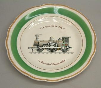 """Vit porslinstallrik med lånad dekor. Ett ånglok i mitten och grön och röd rand. Text: """"LE CHEMIN DE FER 1a Schneider -France- 1865"""""""
