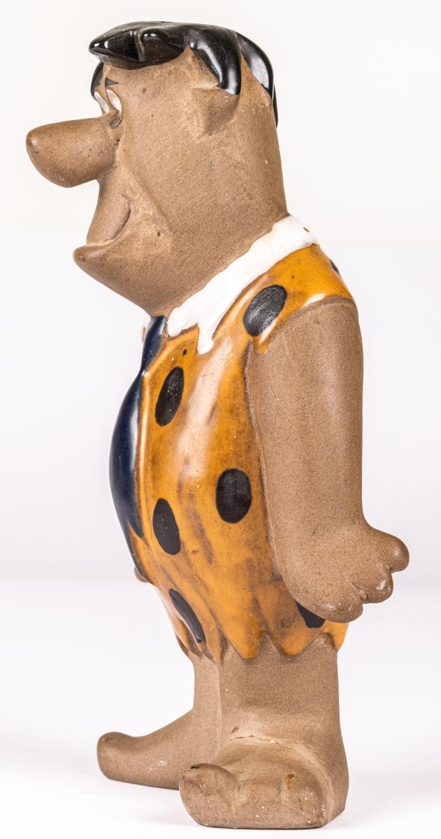 """Figurin i keramik föreställande Fred Flinta (Fred Flintstone) ur serien """"The Flintstones"""" av Dorothy Clough för Gefle Porlinsfabrik/Upsala-Ekeby, 1962."""