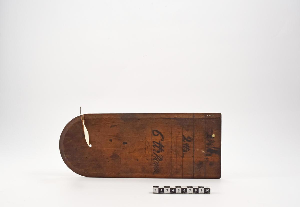 Mall, av trä. Rektangulär med ena änden sfärisk. Den användes för tillverkning av karduser. Mallen är avmärkt med skåra för de olika måtten. Långsidorna och den sfäriska delens kanter är avfasade. Märkt: 2 3/8 u o c, 2 u o c, 6 u: Kanon samt kronstämpel.