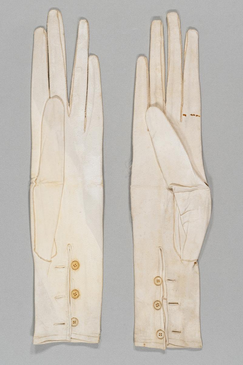 Hanske-etui av skinn, med messingbeslag. Rektangulær form med avrundede hjørner og bunn med belgkonstruksjon. Elfenbens'pren' eller hanskeutvidelsesverktøy med utskjæringer. Inneholder et par hvite, ubrukte skinnhansker med tre knapper på innsiden av håndleddet. Den høyre hansken er revnet oppå hånden og i sidesømmen på begge sider. Har tilhørt Sara Fabricius.