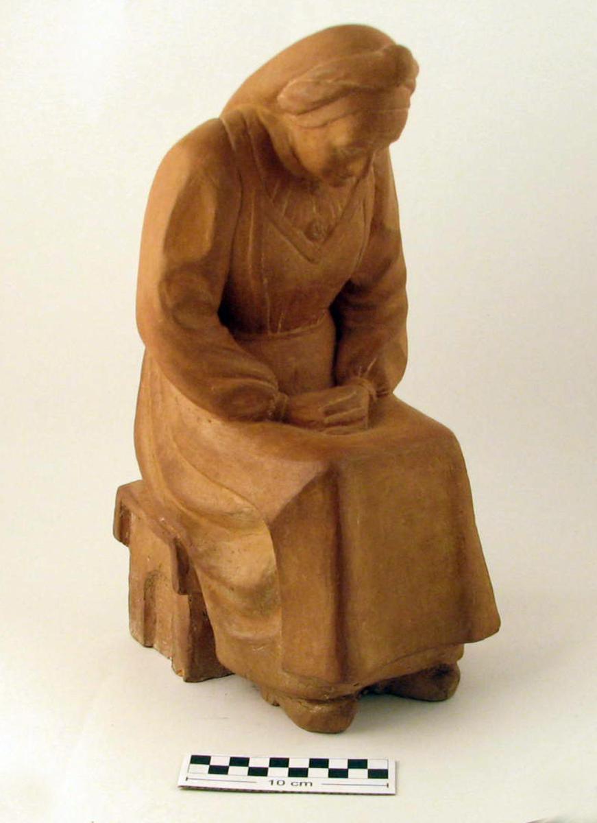 Sittende kvinnefigur. Eldre kvinne, frontal, hodet bøyd, hendene foldet i fanget.