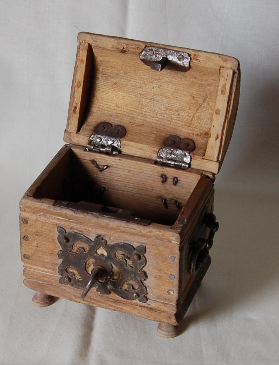 4 ben, rektangulær bunn, rette sider med profiler, buet lokk, jernbeslag, låsbeslag med gjennombrutt dekor, hanker på kortsiden, 2 hengsler, nøkkel.