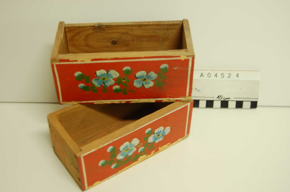 """To identiske skuffer. Rødmalt m. blå og hvite blomster, grønne blad, hvit rand. Malingen slitt i underkant.  """"Håndtak"""" - oprinnelig messingknotter, mangler."""