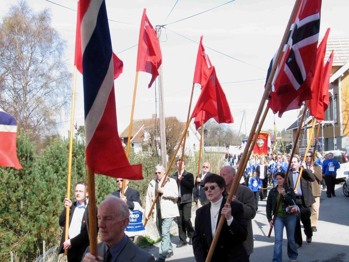 1.mai på Eydehavn. Flaggborg med norske og røde flagg. Tog fra Folkets Hus, her i  Trygve Næss`vei.