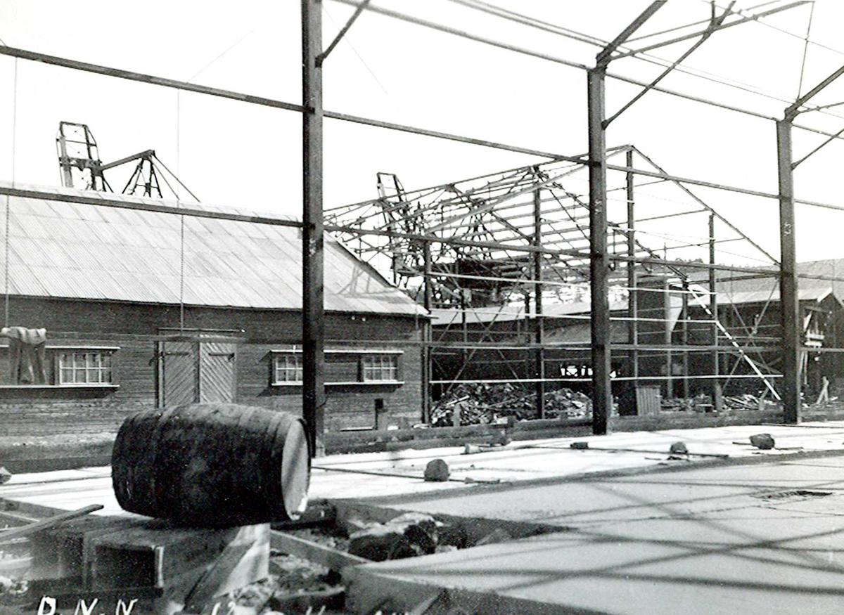 """""""12/04-1924"""" Nitriden. Bygging av stekeribygning for steking av elektrodekull. Jernkonstruksjopner. Tjæretønne og lagerbygning for ferdigvarer til venstre. Kraner på kai i bakgrunnen."""
