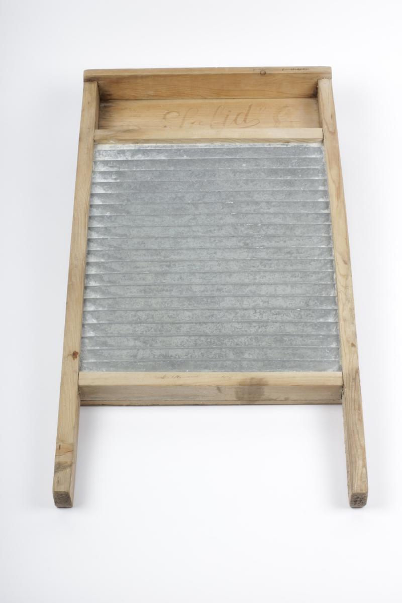 """Form: Bølget Vaskebrettet har bølget blikkplate innfelt i treramme, tre- plater på baksida av blikkplata. Rom for såpe øverst (med innskrift) Tidl. reg.: """"Vaskebrett fra ca. 1900"""""""