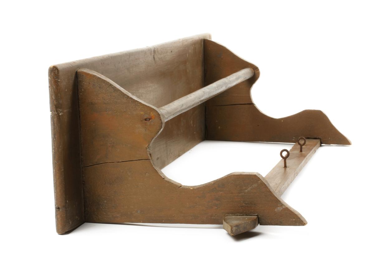 Under hylla profilert knekt på hver side, spikret. Mellom knektene er spikret en sirkulær tverrpinne til bruk for pyntehåndkle (reg.) Fals i den nedre enden på hver knekt, et tverrstykke spikret i falsene. Tverrstykket har en spiss i hver ende, 3 øyeskruer, til oppheng av f.eks. håndklær (reg) To øyeskruer festet til hylla, til bruk for oppheng.
