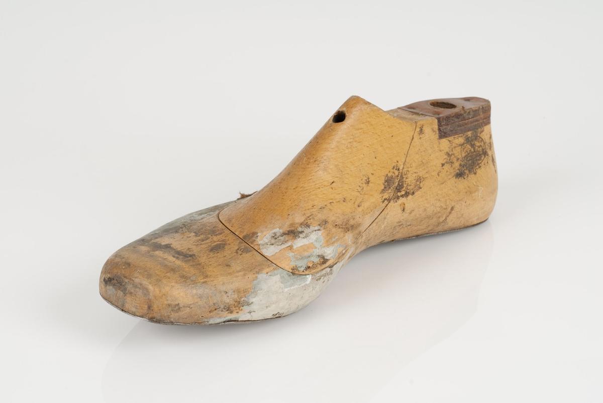 En tremodell i to deler; lest og opplest/overlest (kile). Høyrefot i skostørrelse 45, og 8 cm i vidde. Såle i metall. Lestekam i skinn.