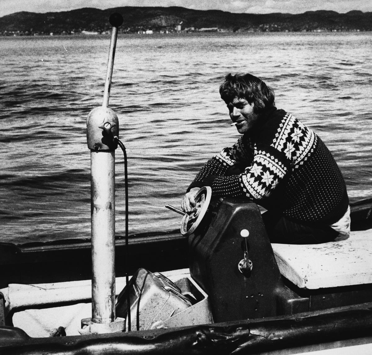 Mann sitter ved ror ombord på båt.