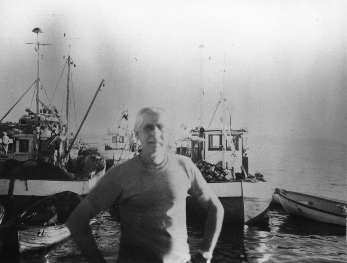 """Mann på kaia med flere fiskebåter i bakgrunnen. """"Johan på brygga"""" drev fiskemottaket i Son i en årrekke."""