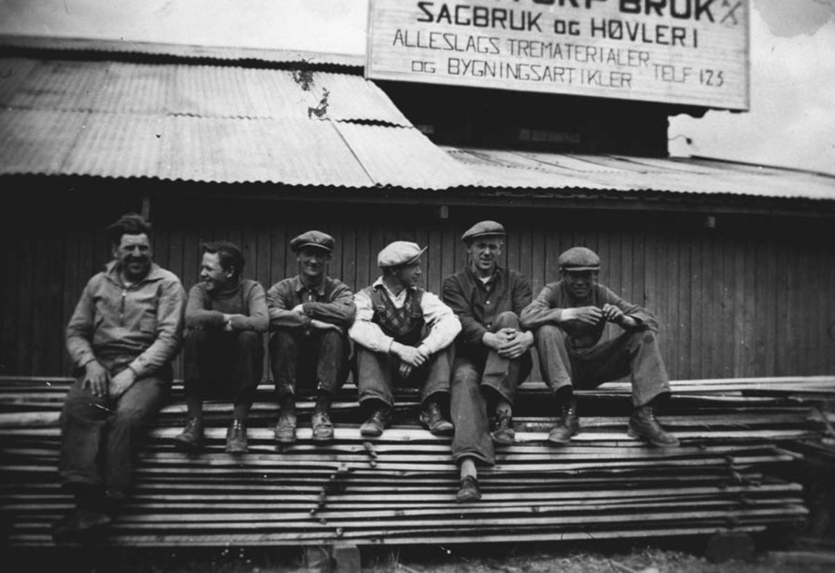 Ansatte ved Drømtorp bruk hviler på en plankestabel.