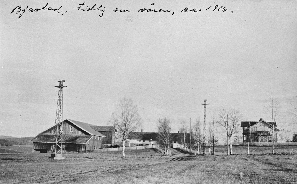 Bjostad gård, 2 bolighus og låvebygning medinngjerdinger. To markante stålmaster leder et linjespenn forbi gården.