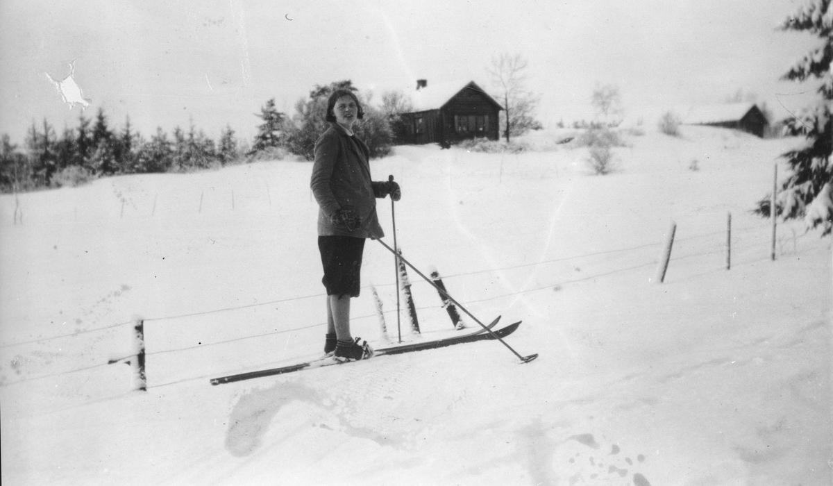 En kvinne på ski foran småbruket Høyås.