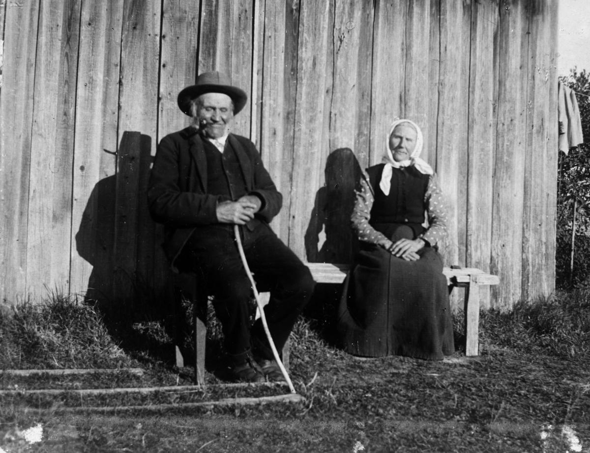 Ektepar sitter ved husveggen, på en benk solskinnsdag