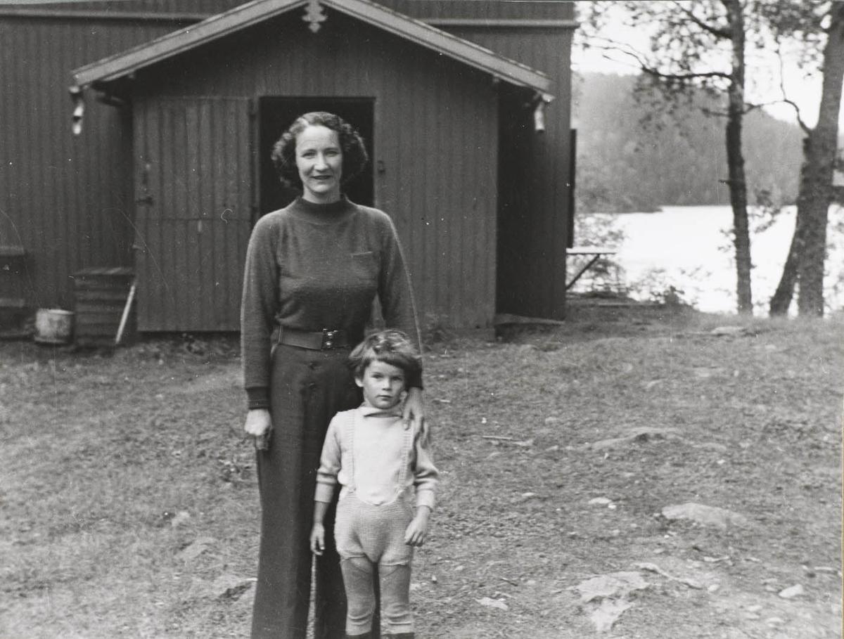 To personer, dame og gutt utenfor hus ved vann