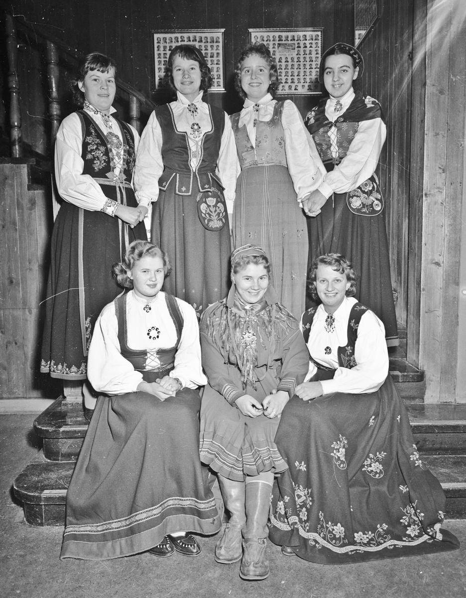 """7 jenter i ulike bunader. """"Ungdomsskolen Hurdal Verk"""" står på bilde i bakgrunnen."""