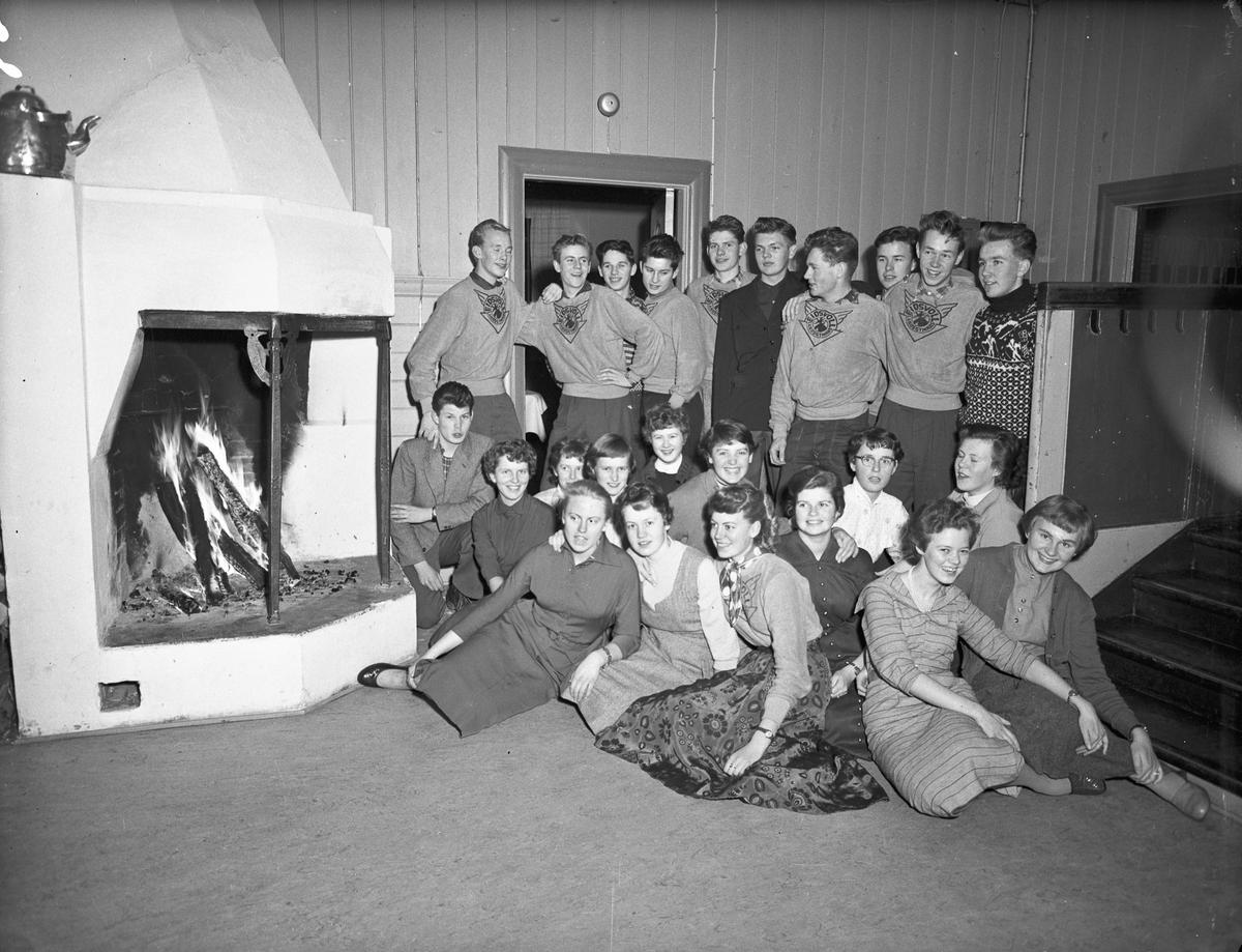 """Ungdommer i en peisestue. """"Eidsvoll Landsgymnas"""" står på genserne."""