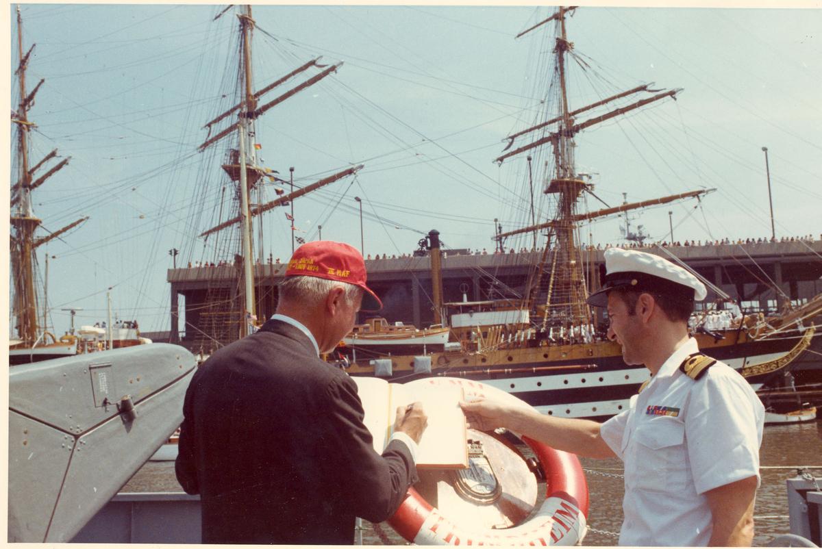 """Oslo-kl.- fregatt KNM """"Trondheim"""" får besøk av Secretary of the Navy J. W. Middeldorf i New York, sommeren 1976. Mr. Middeldorf signerer i offisersmessens gjestebok. I bakgrunnen det italienske skoleskipet Amerigo Vespucci."""