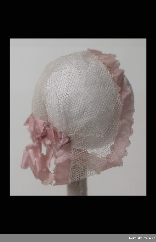 Inventering Sesam 1996-1999: L 10 cm Dockhårklädsel av vit tyll i form av hätta, kantad med rosa sidenband och rosett baktill. Hör till docka inv.nr. 202.174 Leif Wallin jan 1997