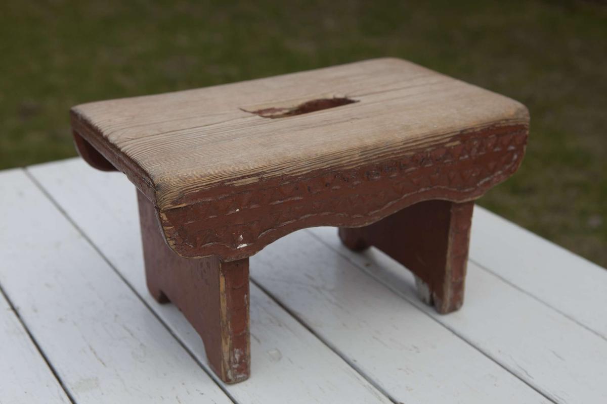 Pall av trä, målad rödbrun. Karvsnittsdekor på långsidorna och benens kortsidor.