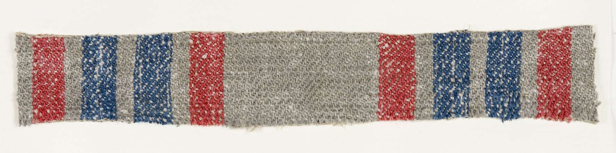 """Vävprov ämnat för bolstervarstyg vävt med bomulls- och lingarn, kypert. Randigt i rött, blått och grått. Vävprovet är uppklistrat på en kartong i storleken 22 x 28 cm. I övre högra hörnet finns en stämpel """"Uppsala läns hemslöjdsförening"""" och ett handskrivet nummer, """"A.1624""""."""