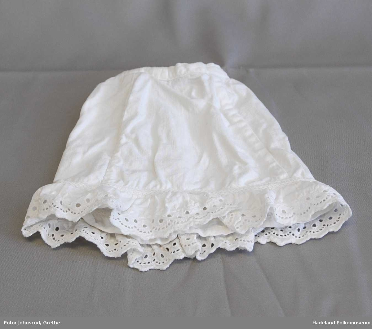 Hjemmesydd tøy til dukke. a: Skjorte b: skjørt i samme stoff som skjorte, c: hvitt underskjørt, d: lavendelblå kyse. a og b er i kremhvit bomull med trykte småruter. Begge har påsydde rysjekanter. c har rysjekant med hullblonde.