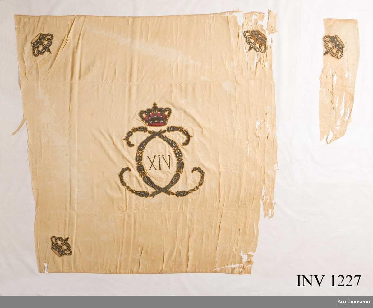 """På det gulvita kyprade fansidenet sitter i mitten ett broderat monogram föreställande två motställda """"C"""" inneslutande """"XIV"""". Broderiet utfört i plattsöm med silke och silvertråd. Ovanför monogrammet sitter en kunglig krona utförd i plattsöm med foder i rött silke. I fanans hörn sitter snedställda kronor i brunt silke. Ett fragment av fanan på vilken en av de fyra kronorna sitter ligger löst och hoprullat tillsammans med fanan.Fanspetsen har Karl XIV Johans monogram, dock mycket ärgat. Fanstången är gulvitmålad. Kravatten, den lilla del som återstår, är uppsydd på ett bomullsband.   Samhörande nr är 25394:1, 25394:2, 1224-1228."""