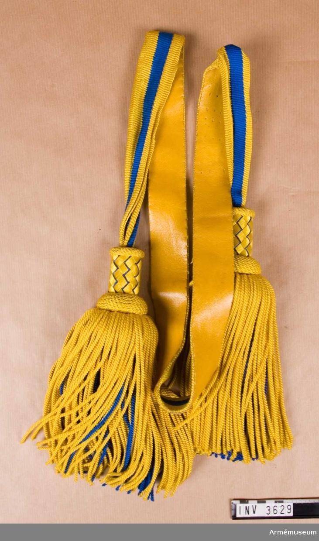 """Längd: 1390 mm + tofs 290 mm.Skärp m/1819-1829, kompaniofficer, A 1. Av silke, virkat med  två gula och två blå ränder. Tofsar i ändarna med korgflätad  Överdel i blått och gult. Tofsen är i """"drejat silke"""", gult på  utsidan och blått innanför i samma grovlek och längd. Skärpet  är fodrat med gult skinn. Förmodligen buret av kadett E Holmer, son till Carl och Dagny  Holmer. Kadett E Holmer tillhörde Svea artilleriregemente, A 1."""