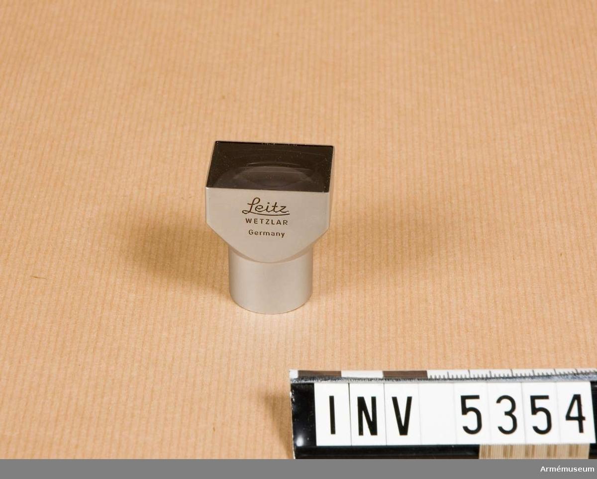 M 3299-1001. Sökare, även kallad spegelsökare, för Leica kamera och objektiv  med brännvidden 35 mm. Sökaren fästs i kamerans sko för olika  tillbehör. De gängade Leicakamerorna saknade inbyggd sökare för  35 mm vidvinkelobjektiv. Objektiv med denna brännvidd hade en bildvinkel på 64 grader. Det har med tiden blivit en av de  vanligaste brännvidderna vid sidan av normalobjektivet 50 mm. Emballage i kartong, två delar. Enligt påskrift på detta är  sökaren avsedd för objektivet Summaron f= 3,5 cm, men även andra objektiv med olika namn men samma brännvidd har funnits, varför sökaren utan vidare torde kunna användas även till dessa. De ljusstarkare objektiven Summicron 2/35 och Summilux  1,4/35 torde ha presenterats i slutet av 1950-talet eller i  början av 1960-talet.Sökarens mått: 40 x 25 x 30 mm.1992-02-27 packad i låda / Erik Walberg.