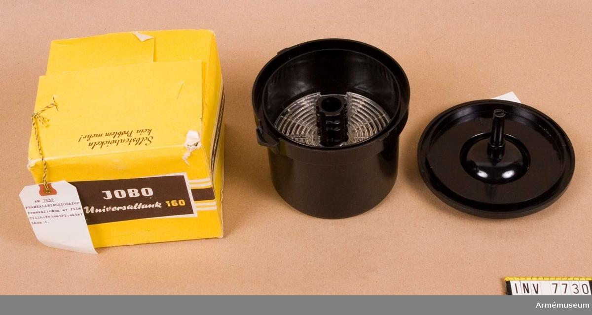 """Användes för framkallning av film. Består av behållare, lock, vridstift, allt av svart bakelit, och ställbar spiral av klar plast, med svart kärna, för upplindning av filmen. Filmformaten kan vara 135, 127, 120 och större format D8 (5,5 x 11 cm).  På  undersidan märkt med bl. a. """"1957"""".   Levererad i originalförpackning av gul kartong med två stycken etiketter: """"M 6717-011 Framkallningsdosa"""" och """"Arto 2122"""". Det  senare var firmanamnet på en fotografisk agentur i Sverige.  Ingår i fotomaterielsats 7 låda 1."""