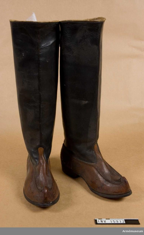 """Grupp C I. STÖVLAR av svart smorläder med upphöjda spetsar (Lapplandsmodell) och 400 mm skaft. På skaftens baksida finns en urklippning och rem med spännen. På sulan står """"42"""" - storlek. """"Eino Gylden"""" - fabriksnamn. Tillverkad i Finland. Deponerad från Arméförvaltningens intendenturdepartement  modellkontoret. Ur en uniform bestående av vapenrock (blus?), spetsbyxor, pälsmössa, pjäxstövlar, läderbälte och pälsmössa."""