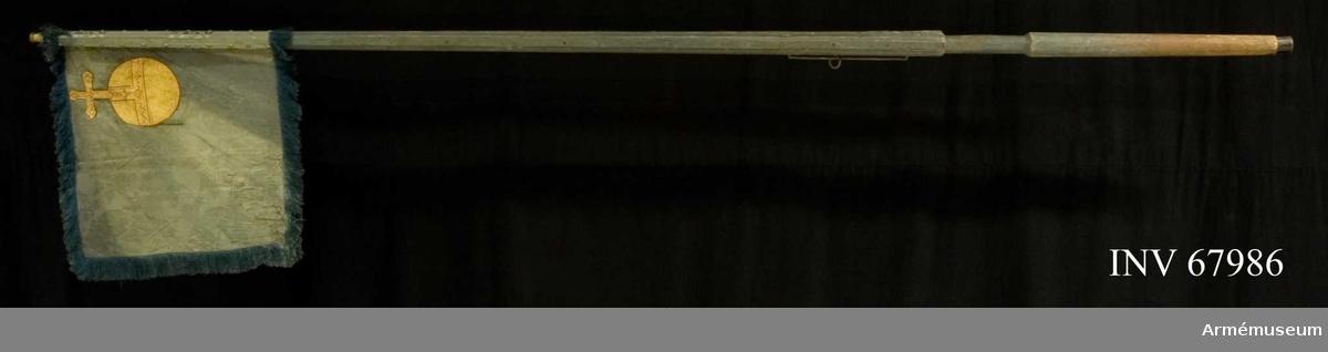 """Duk: Enkel, tillverkad av blå sidendamast med """"bizarre design"""", åtskilligt blekt på insidan och stoppad i nedre, yttre hörnet. Duken fäst vid stången med tre rader tennlikor på blått linneband.  Dekor: Målad lika på båda sidor, i övre, inre hörnet ett riksäpple i guld med konturer i brunrött (Upplands vapen).  Frans:  Enkel, tillverkad av blått silke.  Stång av trä, kanellerad, blågråmålad av järn."""