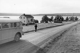 Foton 24/7 1963. Diligensförare är Oscar Rolandsson, från Borgafjäll. Han har kört på linjen i 25 år och är av äkta postsläkt. Fadern var poststationsföreståndare i Borgafjäll och äldste sonen funderar på postiljonsutbildning.  (Se reportage i tidningen PS nr 10/1963) Bussen passerar Ormsjö, västra delen. Utsikt över sjön mot Sörstrand.