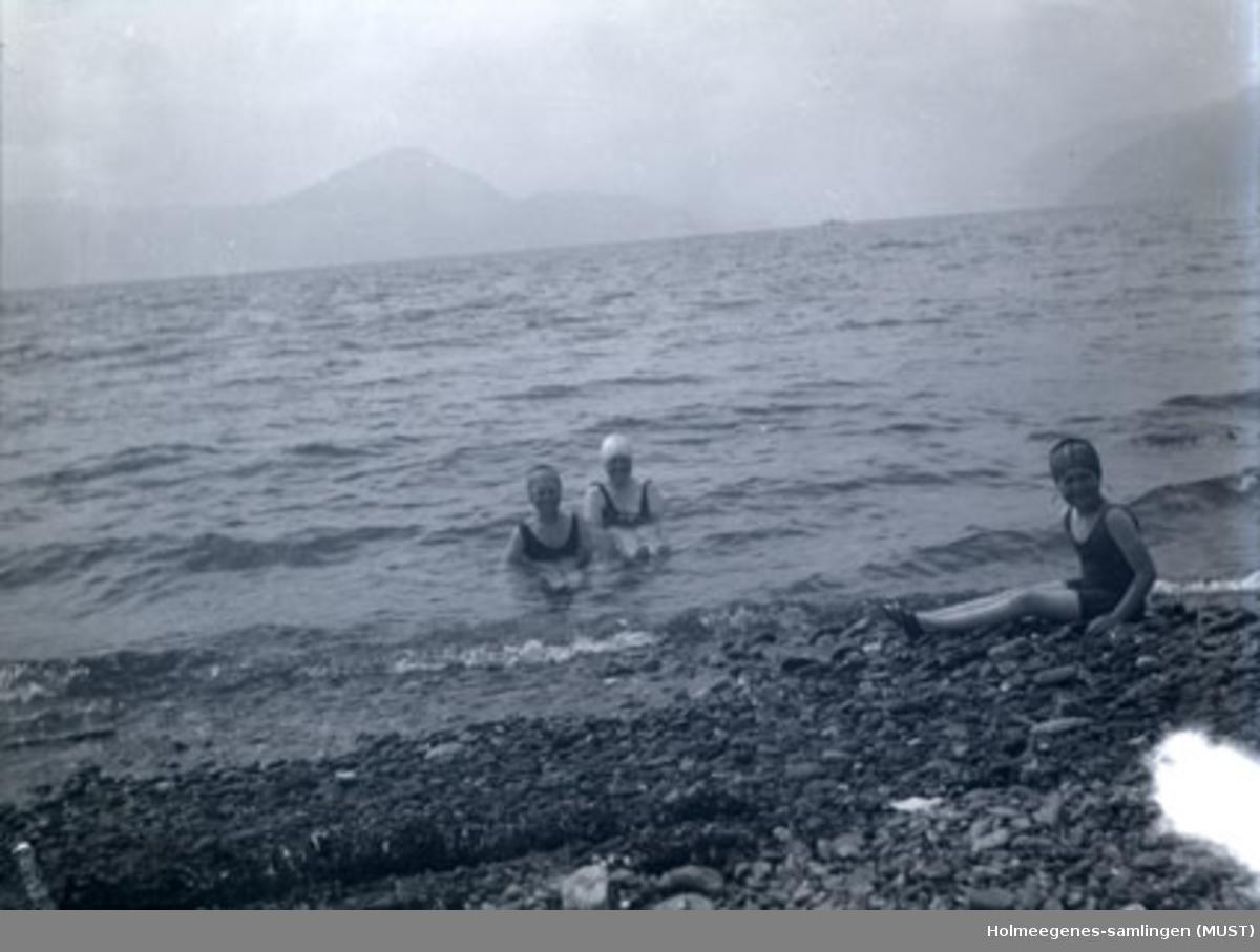 Tre kvinner med badehette og badedrakt bader i sjø med små bølger (bare hode og skuldre stikker opp av vannet). Muligens samme sted og tidspunkt som ST.K.HE 2007-011-0056 og -0057.